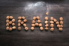 Brain letters sign made with walnuts against wood background. Storm lights. Brainstorming concept. Brain health royalty free stock photo