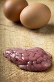 Brain. Pork brain over wood background with two eggs royalty free stock images