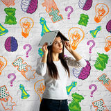 Brain storm concept. Worried girl covering head with laptop on brick background with drawn lamps, brains, question marks, puzzle pieces and other items. Brain Royalty Free Stock Photos