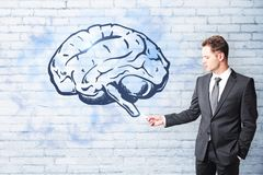 Brain storm and plan concept. Handsome caucasian businessman drawing creative brain sketch on brick wall background. Brain storm and plan concept Stock Images