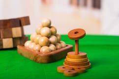 Brain Teaser de madeira ou enigmas de madeira no assoalho verde no fundo borrado Fotos de Stock Royalty Free
