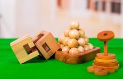 Brain Teaser de madeira ou enigmas de madeira no assoalho verde no fundo borrado Fotografia de Stock Royalty Free