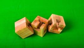 Brain Teaser de madeira ou enigmas de madeira no fundo verde Imagem de Stock
