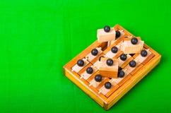 Brain Teaser de madeira ou enigmas de madeira no fundo verde Imagem de Stock Royalty Free