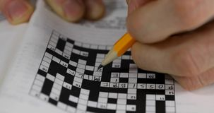 Brain training - hand doing crossword puzzle stock video