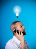 Brainstorm. Man with a beard with a light bulb on the phone stock photos