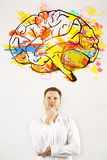Brainstorm concept. Portrait of thoughtful young businessman on concrete background with brain sketch. Brainstorm concept Royalty Free Stock Image