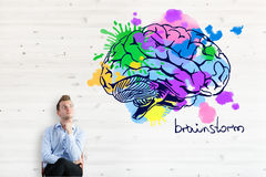 Brainstorm concept. Thoughtful businessman with colorful brain sketch. Brainstorm concept Royalty Free Stock Photo