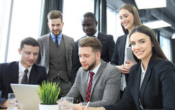 Brainstorm. Group of business people looking at the laptop together. One business woman looking at camera. Brainstorm. Group of business people looking at the Stock Photo