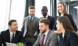 Brainstorm. Group of business people looking at the laptop together. One business woman looking at camera. Brainstorm. Group of business people looking at the Stock Photography
