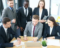Brainstorm. Group of business people looking at the laptop together. One business woman looking at camera. Brainstorm. Group of business people looking at the Royalty Free Stock Image