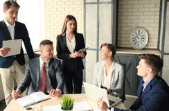 Brainstorm. Group of business people looking at the laptop together. One business woman looking at camera. Brainstorm. Group of business people looking at the Royalty Free Stock Photo