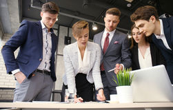 Brainstorm. Group of business people looking at the laptop together. One business woman looking at camera. Brainstorm. Group of business people looking at the Royalty Free Stock Photography