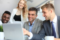 Brainstorm. Group of business people looking at the laptop together. One business woman looking at camera. Brainstorm. Group of business people looking at the Royalty Free Stock Images