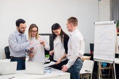 brainstorm Grupo de executivos alegres no vestuário desportivo esperto que olha o portátil junto e o sorriso foto de stock
