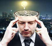 Brainstorm ideas concept. Thoughtful young businessman with abstract concrete maze and illuminated lamp sketch inside head on night city background. Brainstorm Royalty Free Stock Photo