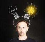 brainstorm Uomo con la lampadina due sul fondo della lavagna Concetto di idea e di 'brainstorming' fotografia stock libera da diritti