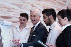 'brainstorming' ομάδας επιχειρηματιών και λήψη των σημειώσεων σε flipboar Στοκ Εικόνα
