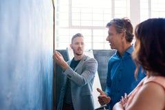 'brainstorming' συναδέλφων εργασίας σε έναν πίνακα κιμωλίας σε ένα γραφείο Στοκ εικόνες με δικαίωμα ελεύθερης χρήσης