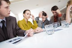 Brainstorming. Photo of several white collar workers brainstorming with pensive expressions Stock Image