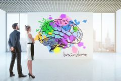 Brainstorming concept. Thoughtful young businesspeople looking at drawn colorful brain in bright concrete interior with city view. Brainstorming concept. 3D Stock Photos