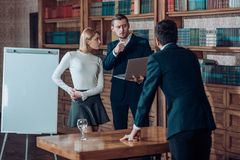 Brainstorming concept. University students hold brainstorming session in library. Business men and woman at. Brainstorming concept. University students hold royalty free stock image