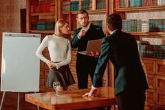 Brainstorming concept. University students hold brainstorming session in library. Business men and woman at. Brainstorming concept. University students hold stock photos