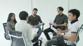 'brainstorming' del gruppo di affari in un cerchio intorno loro sulle sedie stock footage