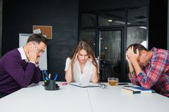 Brainstorming in difficult business situation office workers collegues. Three young people think hard. Teamwork concept Royalty Free Stock Photo