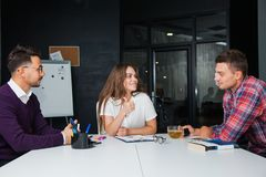 Brainstorming in difficult business situation office workers thumb up. Three young people think hard. Teamwork concept Royalty Free Stock Image