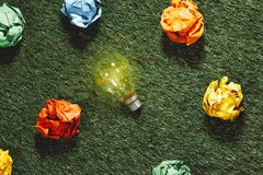 Brainstorming. Great concept with crumpled office paper and light bulb standing on the table stock images