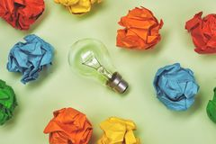 Brainstorming. Great concept with crumpled office paper and light bulb standing on the table stock photos