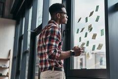 brainstorming Homem novo sério que aplica notas adesivas ao buil fotografia de stock royalty free