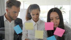 'brainstorming', lavoratori che esaminano il pianificatore della parete di vetro con le note in sala del consiglio, giovane grupp video d archivio