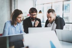 Brainstorming process at sunny office.Group of Young coworkers work together modern office studio.Happy business team. Making conversation.Horizontal.Blurred Stock Image