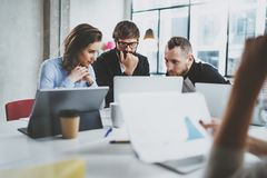 Brainstorming process at sunny office.Young coworkers work together modern office studio.Happy business team making. Conversation.Horizontal.Blurred background Royalty Free Stock Image
