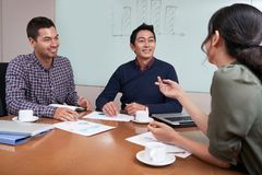 Brainstorming session. Cheerful young business people having brainstorming session Royalty Free Stock Images