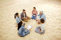 Brainstorming at session. Circle of young players and their trainer sitting on sandy field while gathered for game discussion Royalty Free Stock Photo