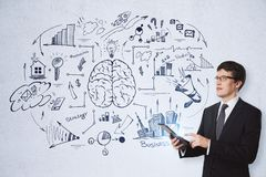 Brainstorming, success and research concept. Handsome european businessman using tablet on concrete wall background with business brain sketch. Brainstorming Stock Photo