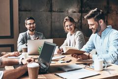 Brainstorming together. Group of young modern people in smart ca royalty free stock images