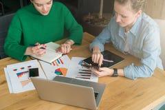 brainstorming Twee jonge bedrijfsvrouwen die bij lijst zitten en businessplan bespreken Stock Foto's