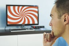 Brainwashed elderly man. Hypnotic spiral on the screen of the TV. The young man hypnotized by false information on the monitor screen. False news on the royalty free stock photos