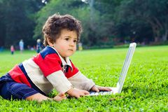 Brainy baby. A brainy baby using a laptop in the park Stock Images