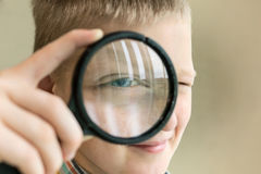 Brainy boy with magnifying glass. Face of brainy blond boy with magnifying glass Stock Image