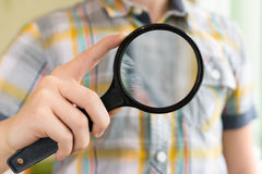 Brainy lad with magnifying glass. Brainy lad explorer with magnifying glass close up Royalty Free Stock Photography