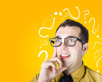 Brainy man puzzle solving on question background. Inquisitive dorky male troubleshooting problem when thinking with look of discovery. Question mark background Royalty Free Stock Images