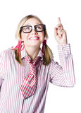 Brainy business woman pointing to copyspace. Brainy young blonde business woman wearing stereotypical nerdy glasses pointing to blank copyspace above her head Royalty Free Stock Photography