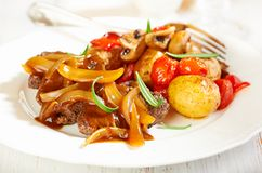 Braised beef with onion sauce and oven baked vegetables stock images