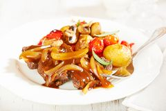 Braised beef with onion sauce and oven baked vegetables stock photos