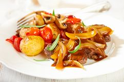 Braised beef with onion sauce and oven baked vegetables stock image
